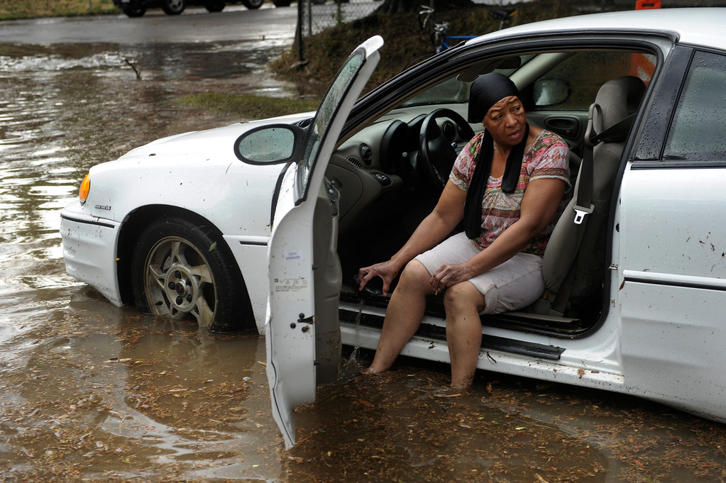 . DENVER, CO. - JULY 13:  Leslie Thompson bailed water out of her car that got stalled in the middle of Martin Luther King Parkway at Eudora Street Saturday. Hard rains across the Denver metro area led to localized flooding Saturday evening, July 13, 2013.  Photo By Karl Gehring/The Denver Post