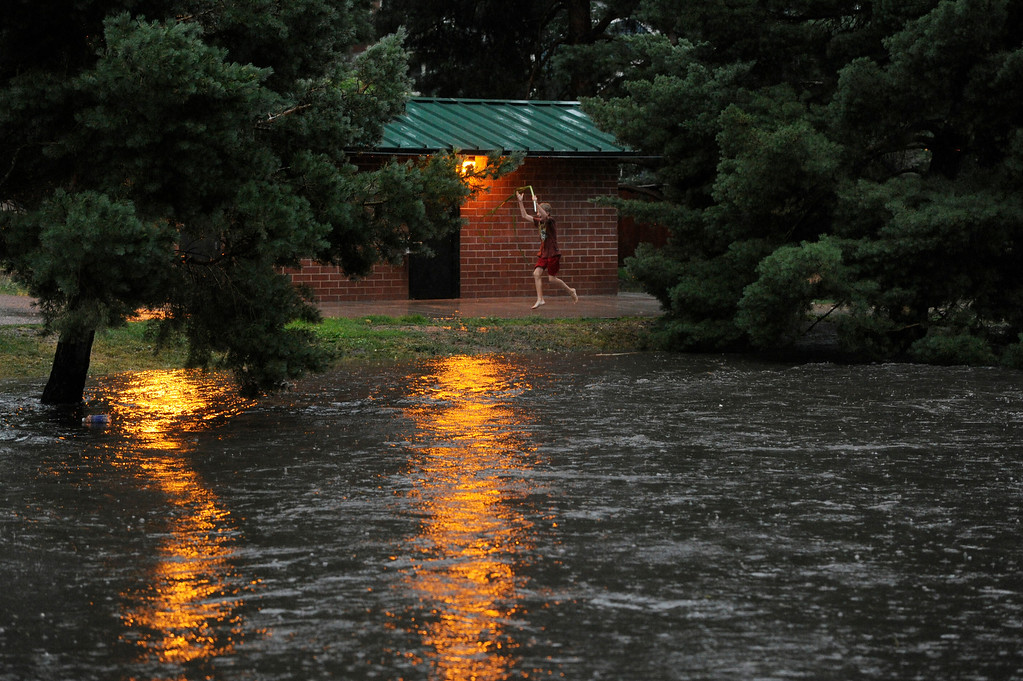 . DENVER, CO - JULY 13:   A boy hops in excitement alongside on outbuilding next to a swollen gulch at McWilliams Park near Yale Ave and Fillmore St. in Denver Colorado, July 13, 2013 after a heavy rainstorm. (Photo By Andy Cross/The Denver Post)