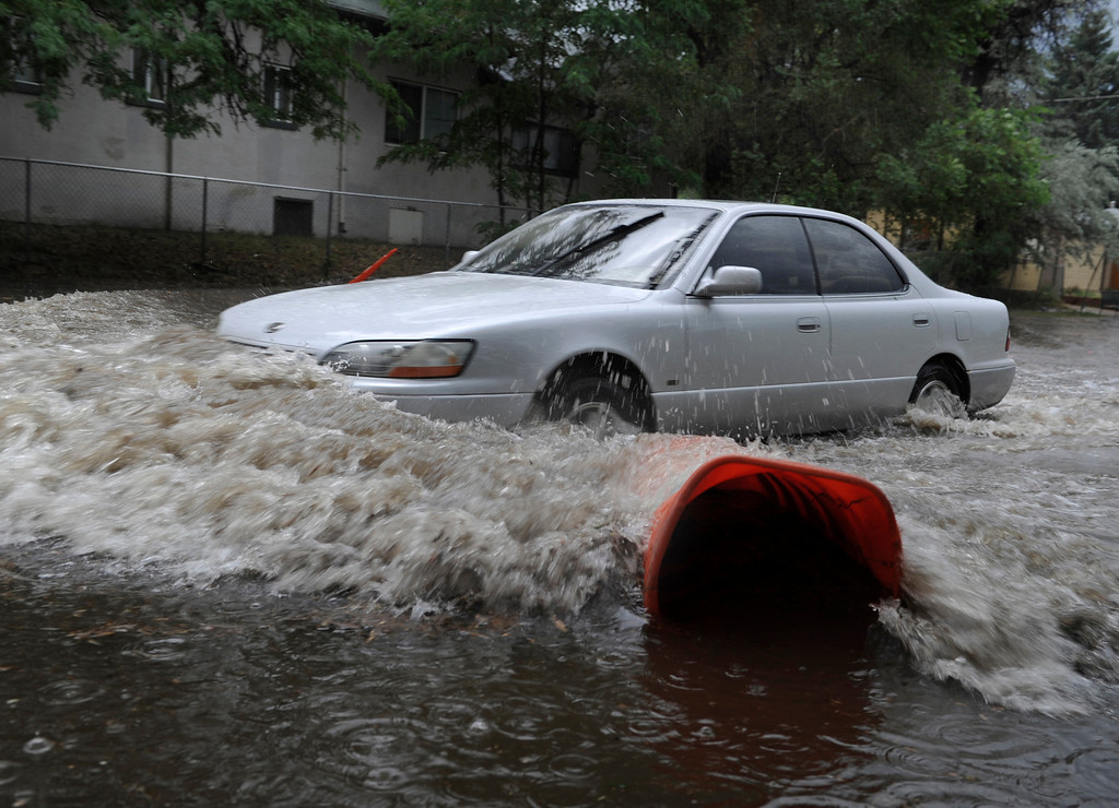 . DENVER, CO. - JULY 13:  A motorist pushed a wall of water ahead of the car driving eastbound on Martin Luther King Parkway Saturday.  Heavy rain fell over Denver Saturday evening, July 13, 2013 causing localized street flooding.  Photo By Karl Gehring/The Denver Post