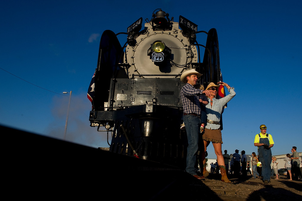 . DENVER, CO - JULY 20: Rick Carpinelli stands with Laura Paquelet and their son, Charles, in front of steam locomotive No. 844 as it rests on Track 20 at the Denver Train Yard during Denver Post Cheyenne Frontier Days on July 20, 2013, in Denver, Colorado. The train is bound to and from Cheyenne, Wyoming. (Photo by Daniel Petty/The Denver Post)