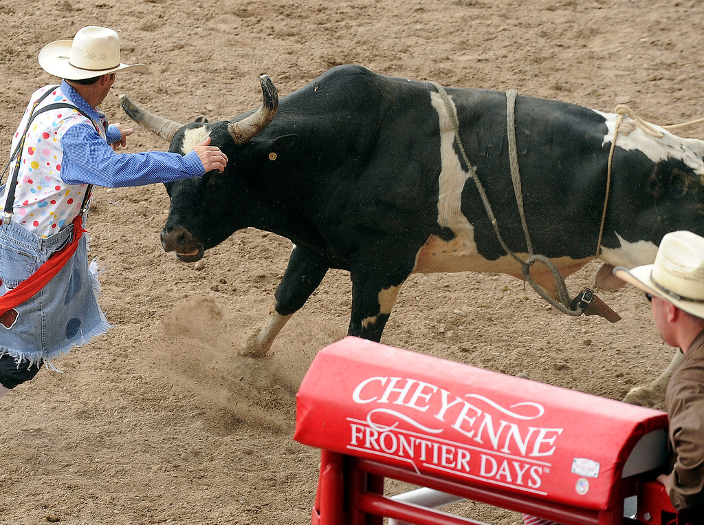 . CHEYENNE, WY - JULY 20: A rodeo clown jumps in to distract a bull during the Cheyenne Frontier Days Rodeo on July 20, 2013, in Cheyenne, Wyoming. (Photo by Anya Semenoff/The Denver Post)