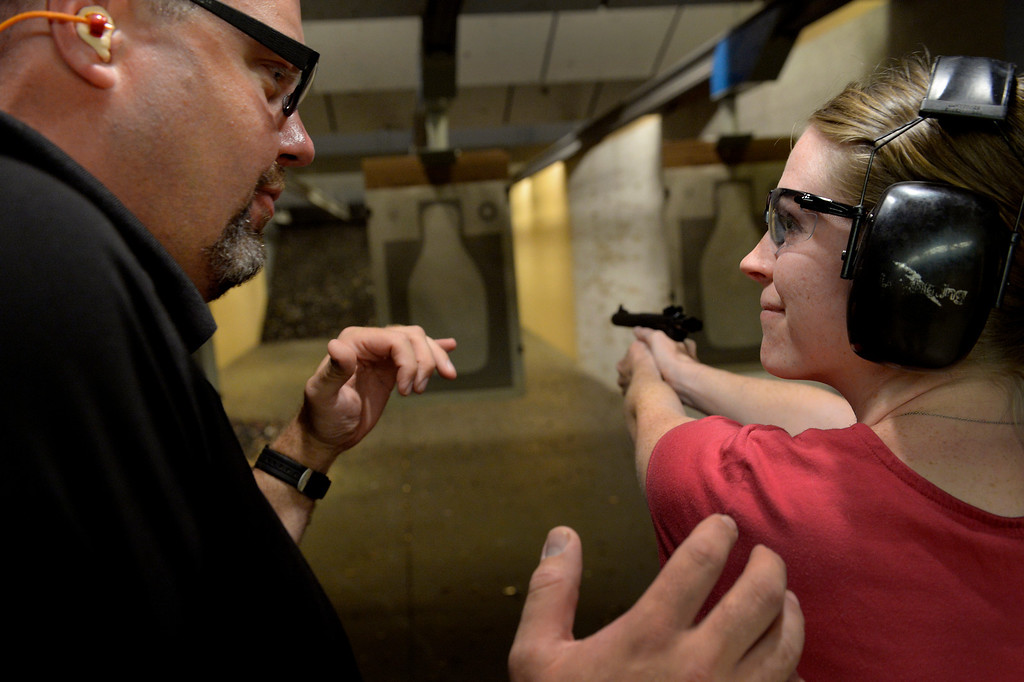 . CENTENNIAL, CO. - JULY 27: Instructor John Abramson, left, works with Catherine Williams during a Multi-State Concealed Carry class at the Centennial Gun Club shooting range in Centennial, CO July 27, 2013. The number of people seeking a concealed carry gun permit in Colorado has increased by 87 percent from last year. Williams said she decided to take the class after seeing a recent video of a New Jersey mother being beaten during a home invasion. (Photo By Craig F. Walker / The Denver Post)