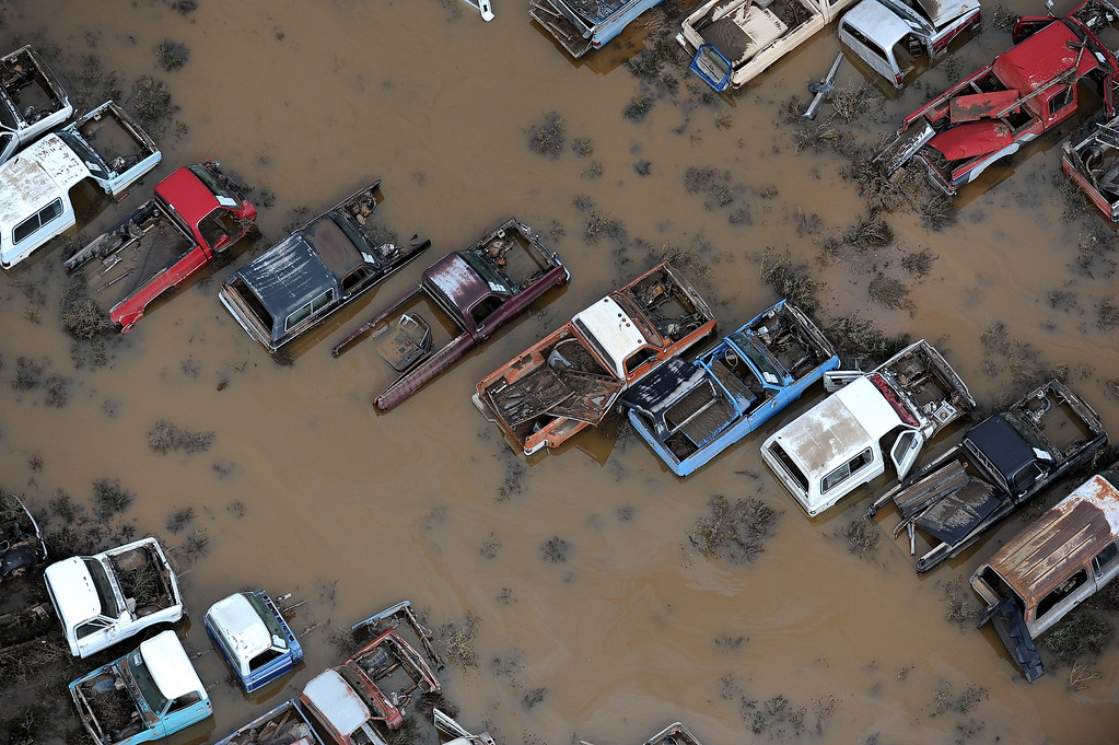 . Cars in a junk yard on 37th Street in Evans,  Colorado, are surrounded by flood waters and mud from the Platte River in Weld County on Monday, September 16, 2013. The flood has devastated cities and farms throughout the county and elsewhere in the state. (Photo By Tim Rasmussen/The Denver Post)