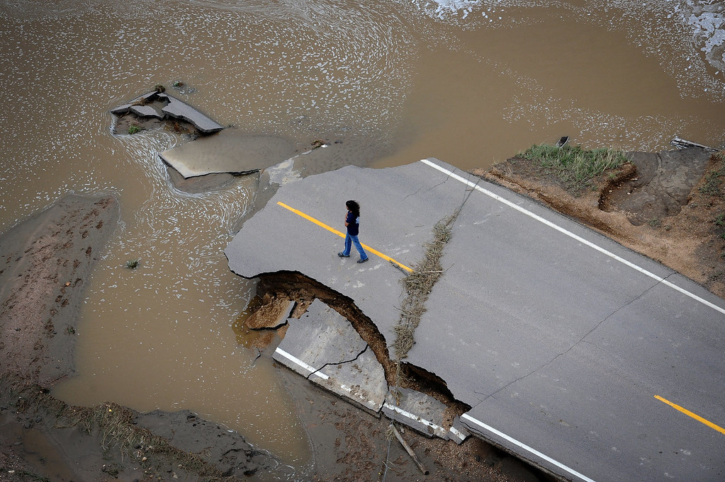 . An unidentified man stands on County Road 61 and looks at the damage caused when South Platte River washed out a major part of the road. Aerial photographs of the  South Platte River flooding cities and farms in Weld County Colorado. (Photo By Tim Rasmussen/The Denver Post)