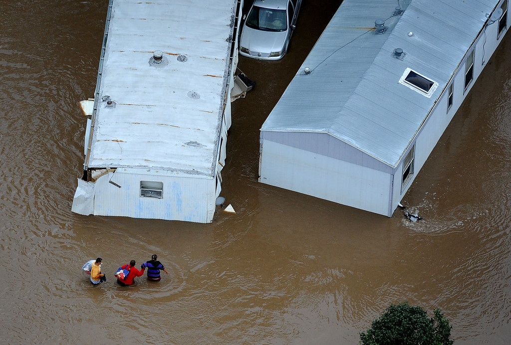 . People walk through waist deep water in a trailer park off of 37th street in Evans Colorado, carrying belongings recovered from flooded  homes in the area. Aerial photographs of the Platte River flooding cities and farms in Weld County Colorado. (Photo By Tim Rasmussen/The Denver Post)