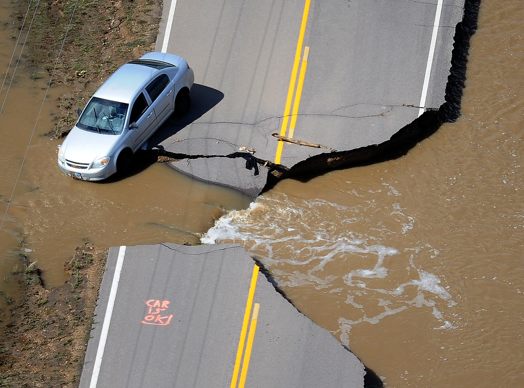 . A car sits partly off the washed-out road near Longmont on Monday, September 16, 2013.   (Photo By Tim Rasmussen/The Denver Post)