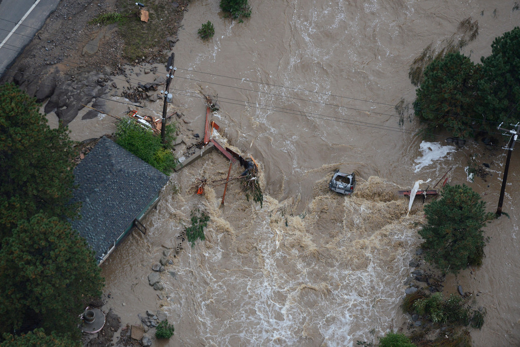 . An SUV remains in the raging Big Thompson River along U.S. 34 in the Big Thompson Canyon in Larimer County Colorado Saturday morning, September 14, 2013. (Photo By Andy Cross/The Denver Post)