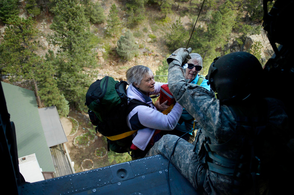 . Two women are hoisted into a UH-60 Black Hawk by Sgt 1st class Keith Bart near Jamestown during a search and rescue flight with members of the 2-4 GSAB with the 4th ID of Fort Carson September 17, 2013 Boulder, CO. (Photo By Joe Amon/The Denver Post)