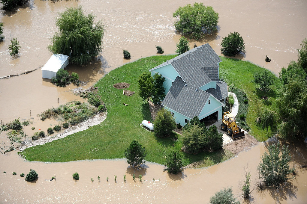 . A home near Evans is surrounded by flood waters from the South Platte River. Aerial photographs of the Platte River flooding cities and farms in Weld County Colorado. (Photo By Tim Rasmussen/The Denver Post)