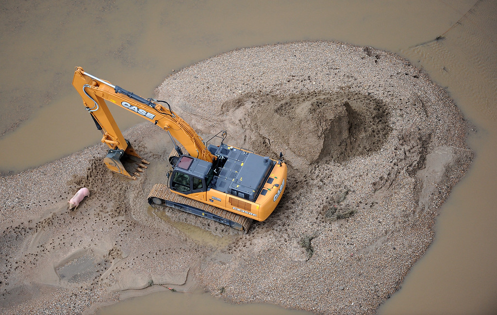 . A pig and a track hoe are stranded on a sanding island in flooded land near Milliken, Colorado, on Monday, September 16, 2013.  (Photo By Tim Rasmussen/The Denver Post)