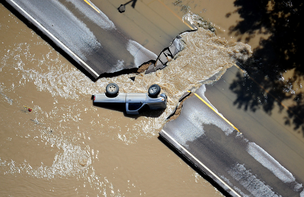 . A truck lays on its side in the floodwaters on a breached section of a road near Longmont on Monday, September 16, 2013. (Photo By Tim Rasmussen/The Denver Post)