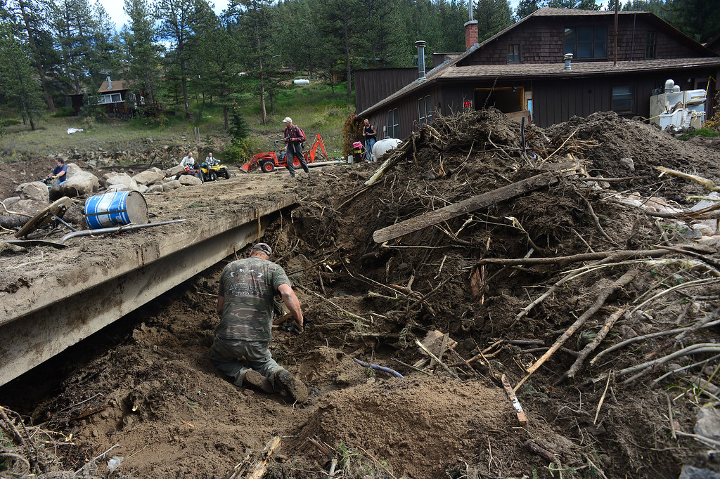 . GLEN HAVEN, CO - SEPTEMBER 30: Glen Haven resident Rick Gdovicak hand digs compacted dirt, mud,  large rocks, trees and debris to clear out a clogged culvert on North Fork Road in Glen Haven, Co on September 30, 2013.  (Photo By Helen H. Richardson/ The Denver Post)