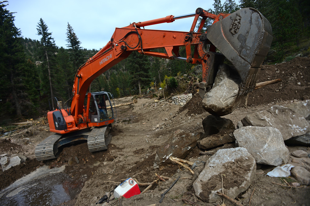 . GLEN HAVEN, CO - SEPTEMBER 30: Travis Sterkel, running an excavator from Kitchen & Company Excavators, cleans large rocks, trees and debris to clear out a clogged culvert on North Fork Road in Glen Haven, Co on September 30, 2013.  (Photo By Helen H. Richardson/ The Denver Post)
