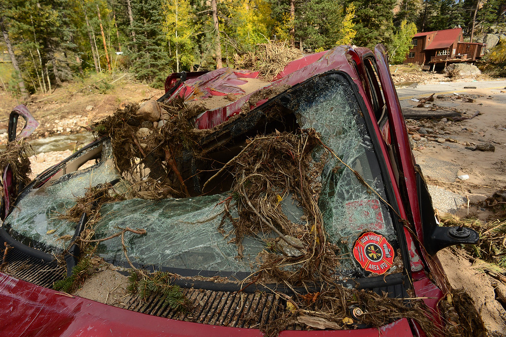 . GLEN HAVEN, CO - SEPTEMBER 30: Main street or Co Road 43 going through the town of Glen Haven, CO is completely gone on September 30, 2013. The road from here to Drake, Co 8 miles down is over 85% destroyed.  this car belonged to Glen Haven firefighter Clifton DeWitt.  He got caught in the flood waters but was able to escape his car and swim to safety.  His car is completely destroyed.  (Photo By Helen H. Richardson/ The Denver Post)