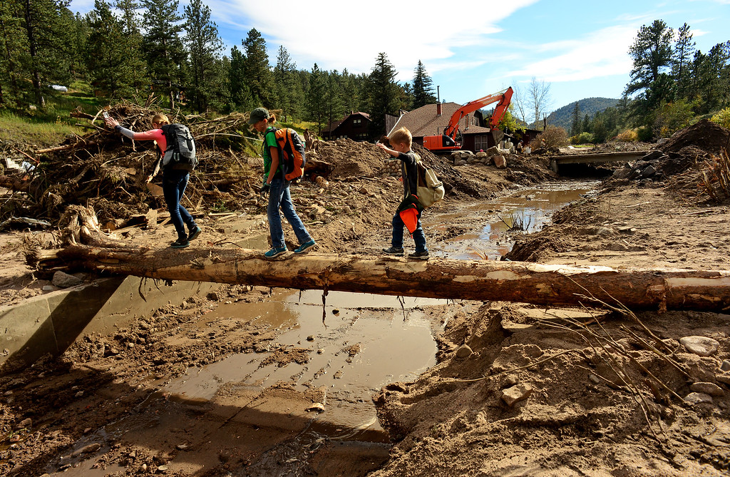 . GLEN HAVEN, CO - SEPTEMBER 30: Lauren Discher, 14, and her siblings Lexie, 11 and Drew, 7 carefully cover a tree above the muddy river bed of West Creek river in Glen Haven, Co on September 30, 2013 as an excavator clears rocks, trees and debris from a culvert.  The Discher family came all the way from College Station, Texas just to help clean what they could in the town and help residents in any way they could.    (Photo By Helen H. Richardson/ The Denver Post)