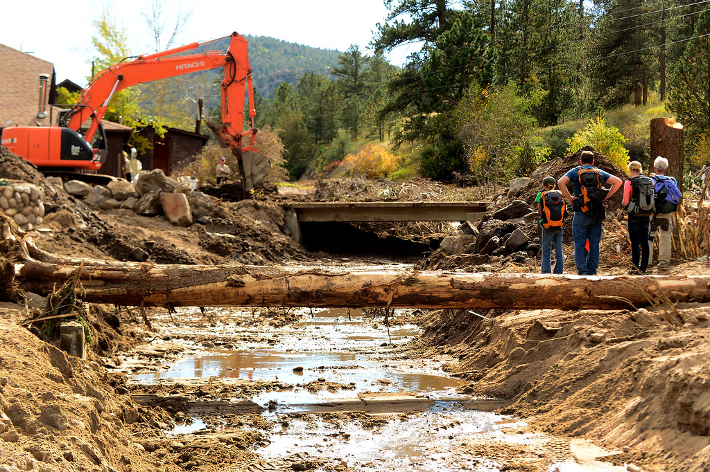. GLEN HAVEN, CO - SEPTEMBER 30: Residents and volunteers watch an excavator clear a culvert along North  on North Fork Road in Glen Haven, Co on September 30, 2013 as it clears rocks, trees and debris.  With little help currently from the outside world, except for the local electric company trying to establish electricity in the community, residents of the small mountain hamlet of Glen Haven, Co are picking up the pieces themselves on September 30, 2013.  Because this culvert was clogged during the flooding, the West Creek river flowing parallel to town took out the bridge on this road and completely changed course. Residents are trying to put the river back to where it was prior to the flood.  (Photo By Helen H. Richardson/ The Denver Post)