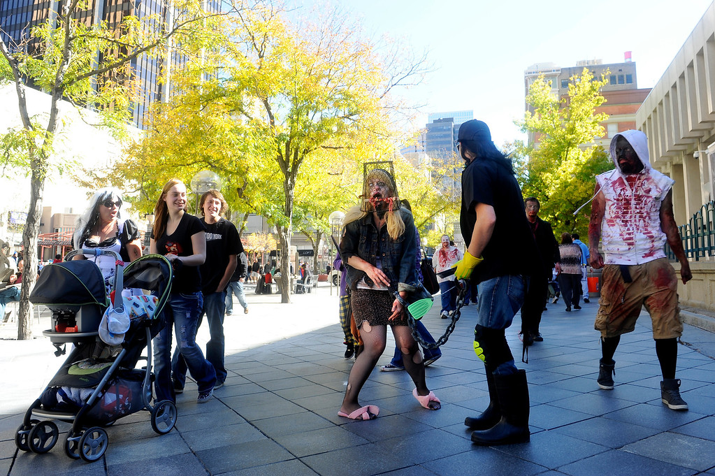. Pedestrians watch as Shanna Thomas and husband Jason Thomas wander down the 16th Street Mall in Denver, CO on Oct. 19, 2013. The couple was participating in the annual Zombie Crawl.  (Photo By Erin Hull/The Denver Post)