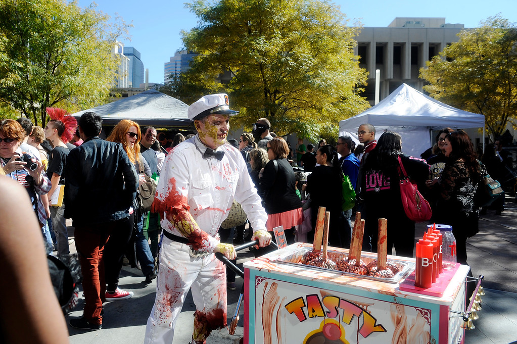 """. \""""Mr. Tasty\"""" pushes his cart of brains on a stick through a plaza filled with other zombies on Oct. 19, 2013 as part of the annual Zombie Crawl.  (Photo By Erin Hull/The Denver Post)"""