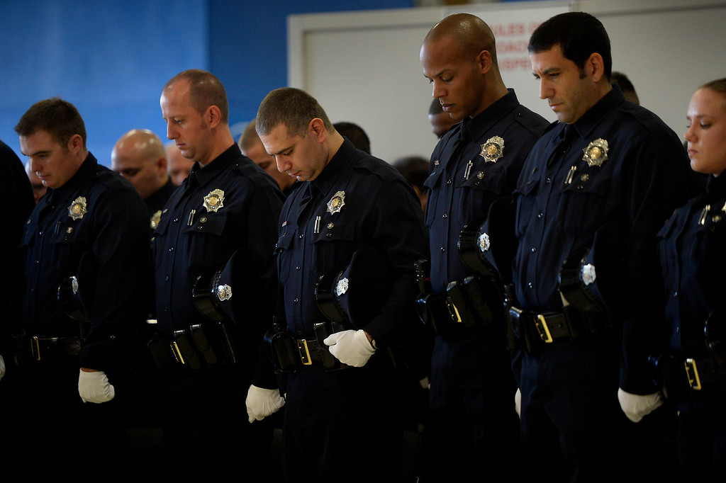 . DENVER, CO. - October 23: Recruits bow their heads in prayer as the Denver Police Department graduates recruits for the first time in five years at the Denver Police Academy. October 23, 2013 Denver, Colorado. (Photo By Joe Amon/The Denver Post)