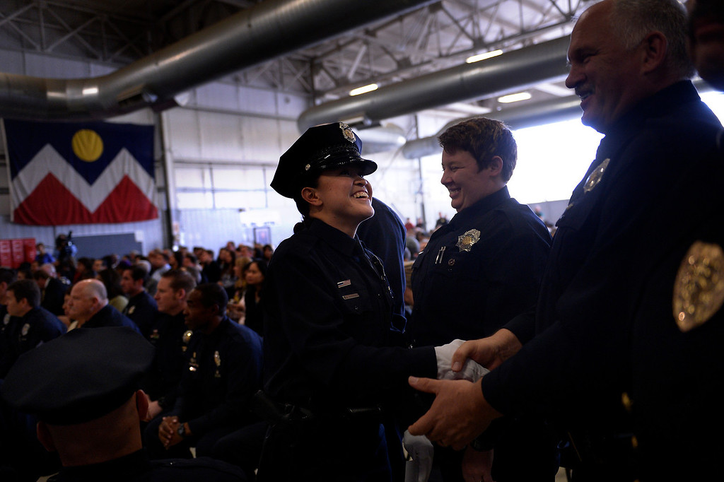 . DENVER, CO. - October 23: Police Officer Alexis Aranda shakes hands with members of the staff of the Denver Police Academy after getting her certificate of completion as the Denver Police Department graduates recruits for the first time in five years. October 23, 2013 Denver, Colorado. (Photo By Joe Amon/The Denver Post)