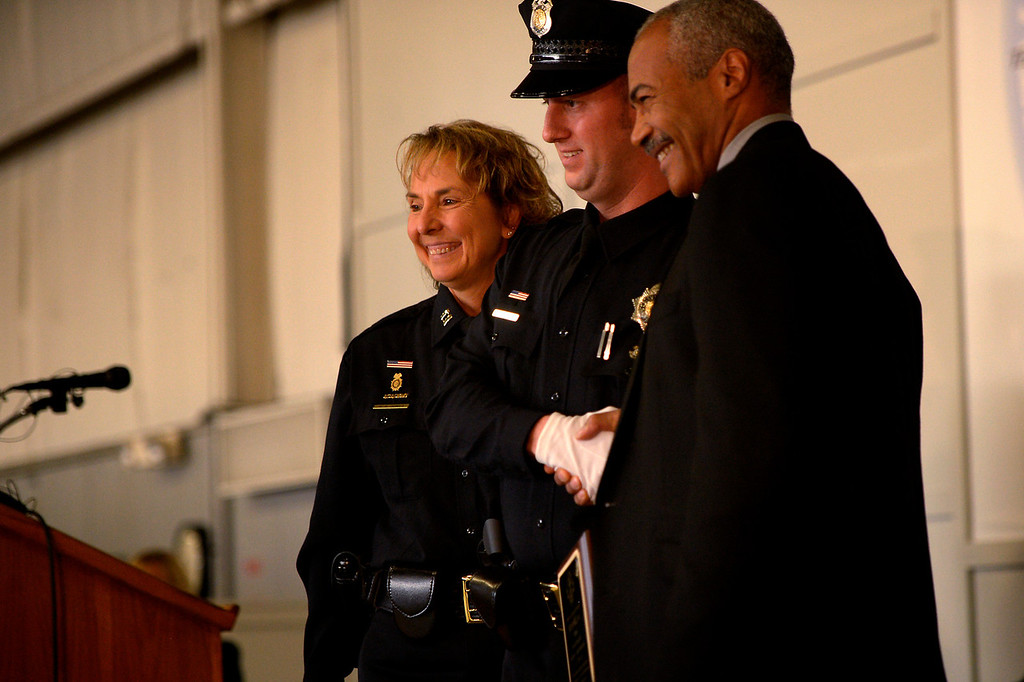 . DENVER, CO. - October 23: Denver Police Department recruit Brian Kaiser receiving the Law award from (left) Captain Rhonda Jones and (right)  Chief Deputy DA Lamar Sims as recruits graduate for the first time in five years at the Denver Police Academy. October 23, 2013 Denver, Colorado. (Photo By Joe Amon/The Denver Post)