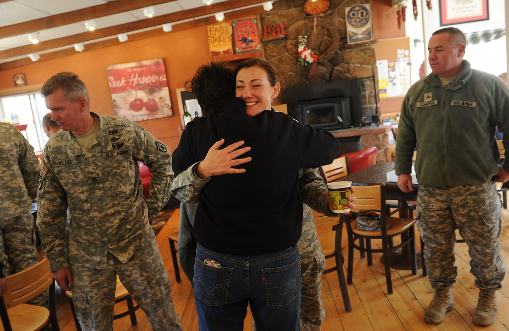 . Pinewood Springs volunteer firefighter Lee Williams hugs Colorado National Guard Staff Sgt. Jecca Geffre  at The Colorado Cherry Company in Pinewood Springs, Co on November 4, 2013.  The Colorado Cherry Company held a pie party for everyone in the community including highway workers and national guardsman to celebrate the reopening of Highway 36 through their community as  well as their first official day of reopening their restaurant.  Owners Kristi and Anthony Lehnert didn\'t charge a single person all day for any of the food that they ate.  (Photo By Helen H. Richardson/ The Denver Post)