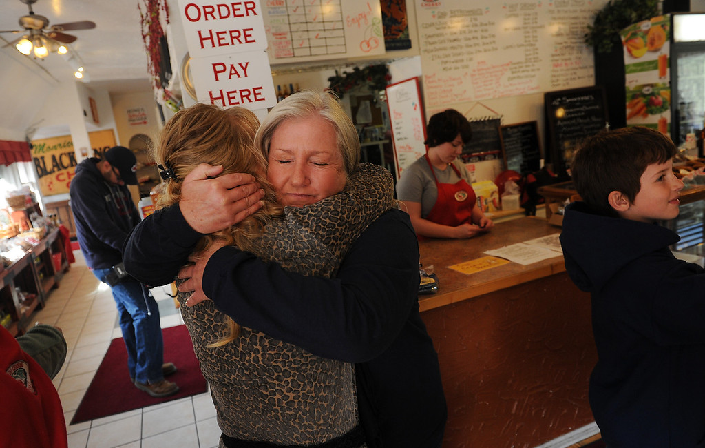 . Pinewood Springs residents Sue Painter, right, hugs Geri Plank, manager of   The Colorado Cherry Company in Pinewood Springs, Co on November 4, 2013.  The Colorado Cherry Company held a pie party for everyone in the community including highway workers and national guardsman to celebrate the reopening of Highway 36 through their community as  well as their first official day of reopening their restaurant.  Owners Kristi and Anthony Lehnert didn\'t charge a single person all day for any of the food that they ate.  (Photo By Helen H. Richardson/ The Denver Post)