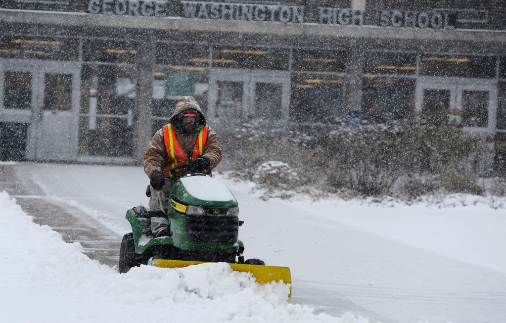 . A worker plows snow in front of George Washington High School near Leetsdale Dr. and Monaco  Thursday morning, November 21, 2013. (Photo By Andy Cross/The Denver Post)