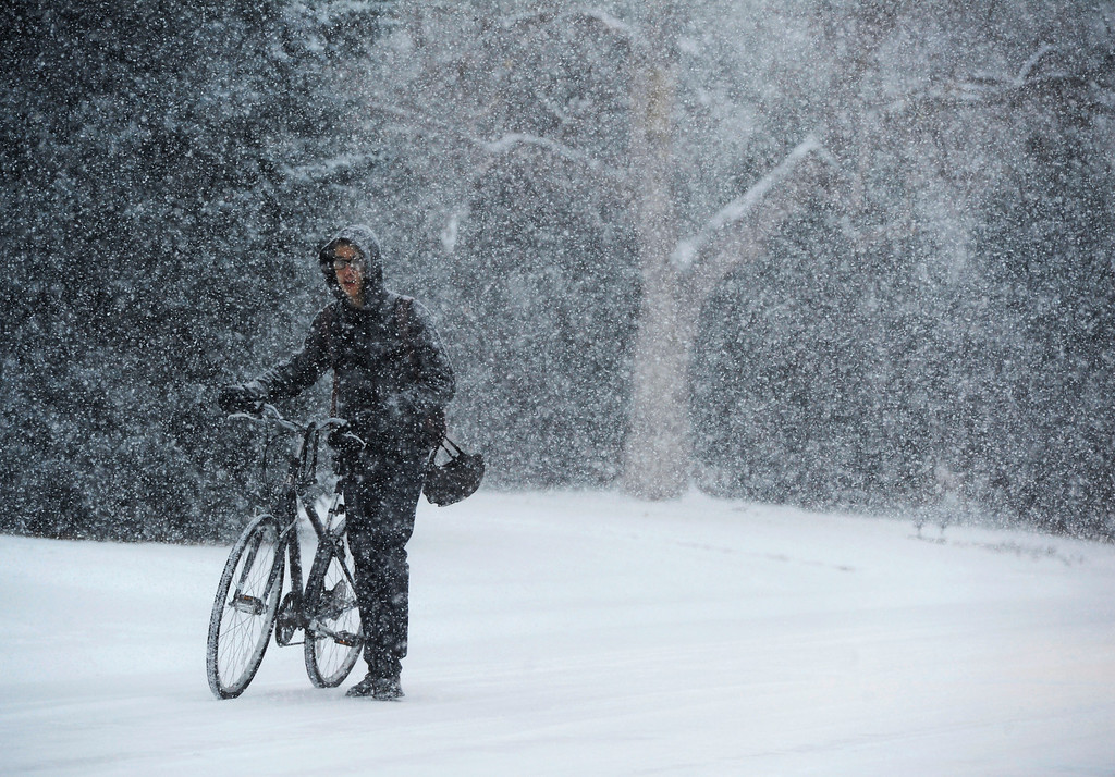 . Denver School of the Arts orchestra major, Ben Roberts, pushes his bicycle through the snow on his way to school near 21st Ave and Olice St. in Thursday morning, November 21, 2013. (Photo By Andy Cross/The Denver Post)