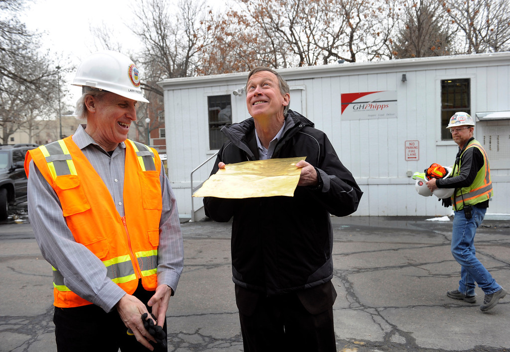 ". State Architect Larry Friedberg, left, gets a laugh as Governor John Hickenlooper pretends to sun himself with section of the 110 year-old gilded copper that was originally on the Capitol dome Friday, November 22, 2013. Progress continues on the restoration of the state Capitol dome, with crews reaching a milestone as they work hidden behind the large white scrim encircling the structure-brand new gold leaf is now being applied over the copper-clad dome. Crews are applying approximately 140,000, 3 1/8"" x 3 1/8\"" gold leaves on top of the copper plates that cover the dome. The leaves are rolled out of 24-karat gold and contractors estimate it will take about 60 ounces of gold to cover the entire dome. (Photo by Kathryn Scott Osler/The Denver Post)"