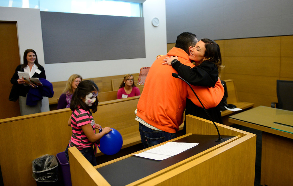 . Gilbert Fernandez gives judge Melanie Gilbert a hug after the adoptions, November 22, 2013. Fernandez is adopting his great niece and nephews who\'s parents are in and out of jail with drug problems, said Fernandez. (Photo by RJ Sangosti/The Denver Post)