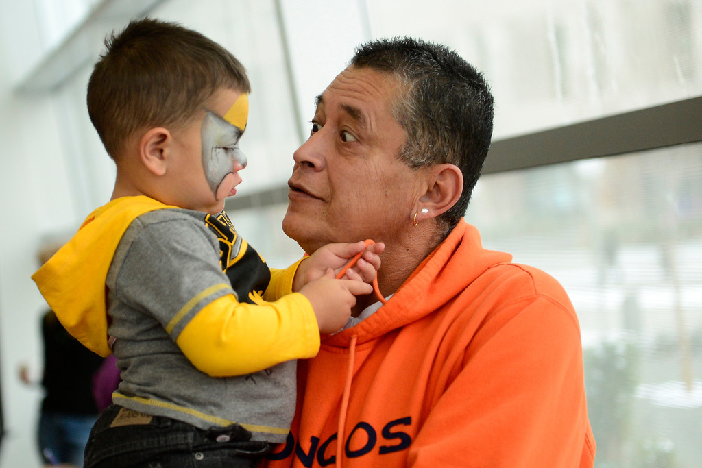 . Gilbert Fernandez checks out the painted face of his great nephew Adam, 18 months, during Denver Adoption Day, November 22, 2013. Fernandez is adopting Adam and two other siblings who\'s parents are in and out of jail with drug problems, said Fernandez. (Photo by RJ Sangosti/The Denver Post)