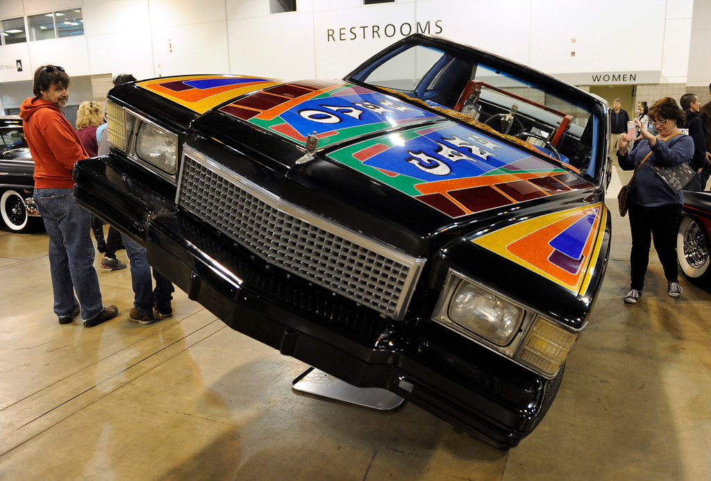 . Jackie Campbell, right, of Englewood, snaps a photo of a 1979 Monte Carlo during the O\'Reilly Auto Parts Creme de la Chrome Rocky Mountain Auto Show takes place at the Colorado Convention Center downtown and runs through Sunday, Dec. 1, 2013. (Photo by Kathryn Scott Osler/The Denver Post)