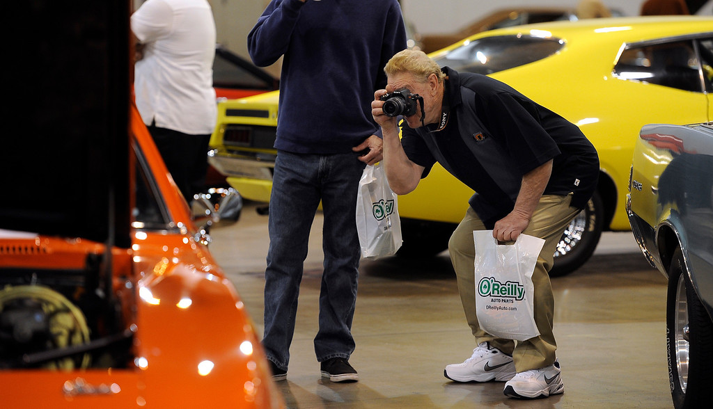 . Roger Myli of Pueblo snaps a photo of a 1969 COPO Camaro Recreation during the O\'Reilly Auto Parts Creme de la Chrome Rocky Mountain Auto Show takes place at the Colorado Convention Center downtown and runs through Sunday, Dec. 1, 2013. (Photo by Kathryn Scott Osler/The Denver Post)