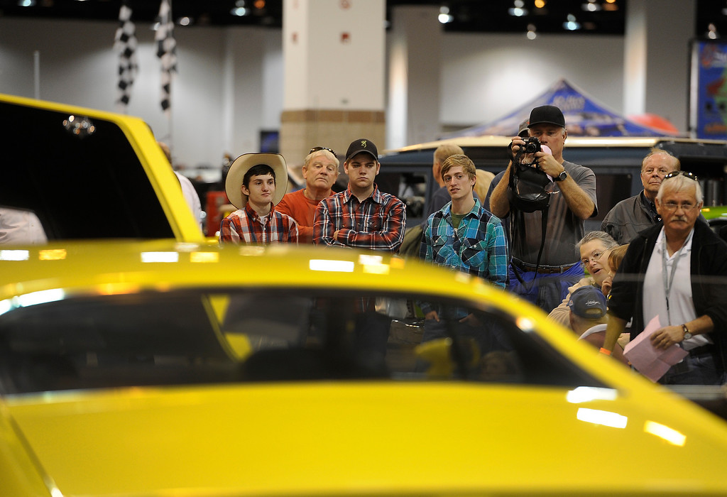 . A crowd gathers as a 1970 Ford Torino Cobra is auctioned off during the O\'Reilly Auto Parts Creme de la Chrome Rocky Mountain Auto Show takes place at the Colorado Convention Center downtown and runs through Sunday, Dec. 1, 2013. (Photo by Kathryn Scott Osler/The Denver Post)