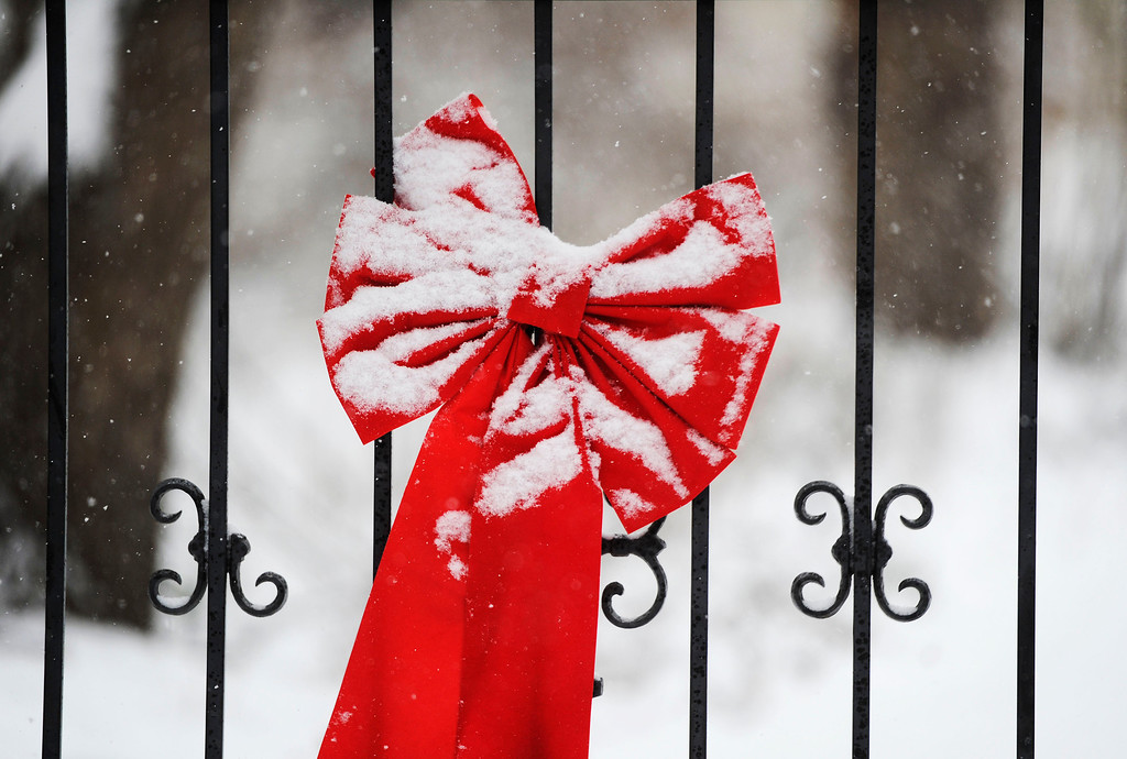. A snow covered holiday decoration adorns a fence along Jackson St. in southeast Denver Wednesday morning, December 04, 2013. (Photo By Andy Cross/The Denver Post)