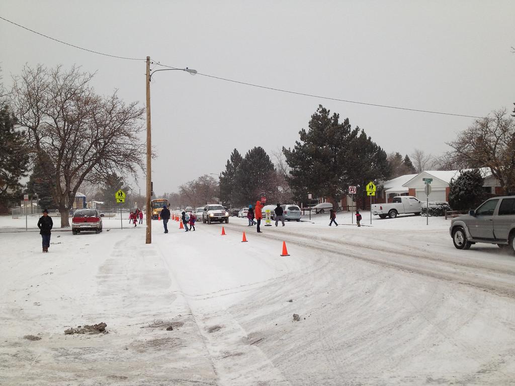 . Parents help their children navigate the icy crosswalk at Virginia Court Elementary School in Aurora on the morning of Dec. 4, 2013. Steve Shultz, The Denver Post