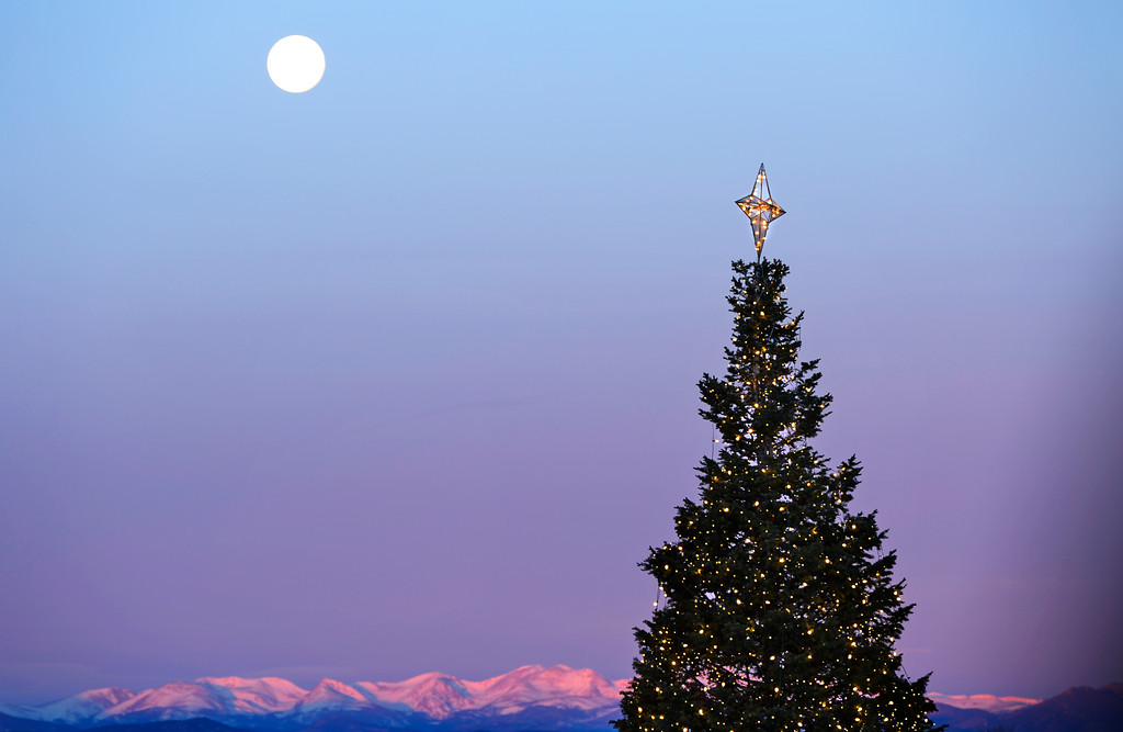 . A full moon is seen over a Christmas tree in Centennial Center Park, December 18, 2013. Forecast are calling for temperatures in the mid 60s for the area. (Photo by RJ Sangosti/The Denver Post)