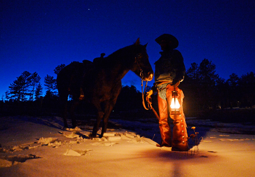 . Tom Jones, a wrangler at Sundance Trail Guest Ranch near Red Feather Lakes, stands with one of the horses after an evening ride, December 20 2013.  The ranch allows guests to ride year-round. (Photo by RJ Sangosti/The Denver Post)