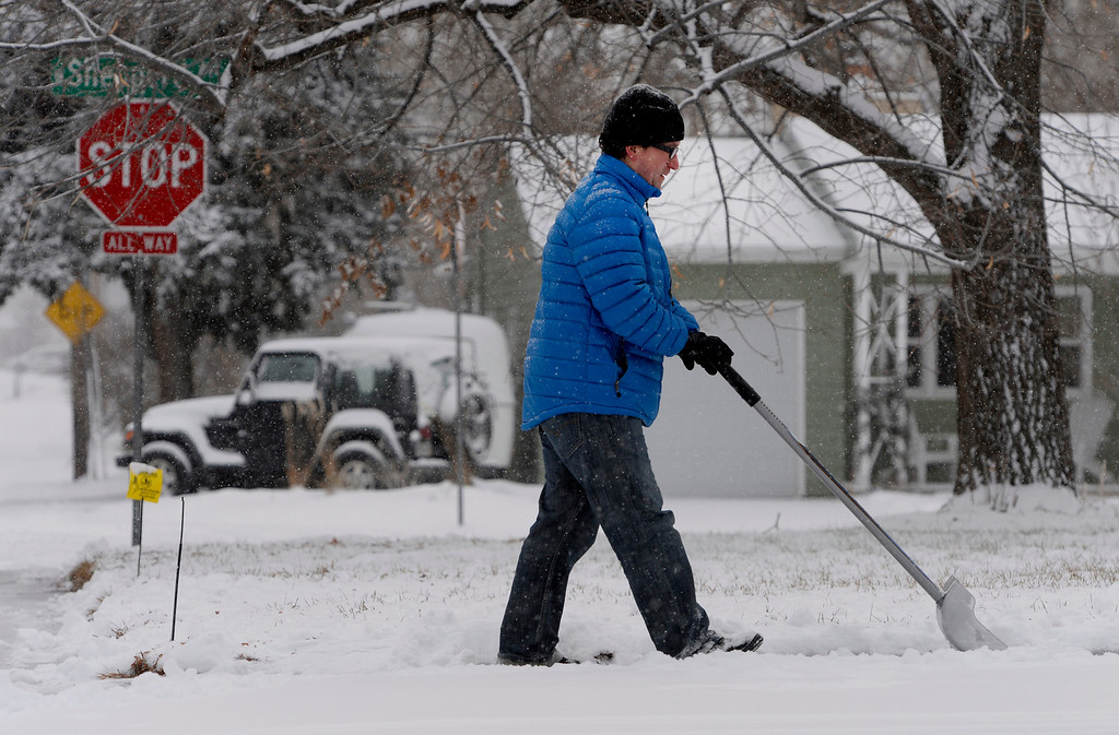 """. Mike Weed shovels snow outside his home in Littleton, CO January 04, 2014. He said, \""""if it\'s going to be winter I\'d rather see it snow... I\'d rather be in the mountains skiing in it.\"""" Temperatures will linger in the low 20s Saturday as a storm drops anywhere from 3 to 5 inches of snow in the Denver metro area, forecasters say. (Photo By Craig F. Walker / The Denver Post)"""