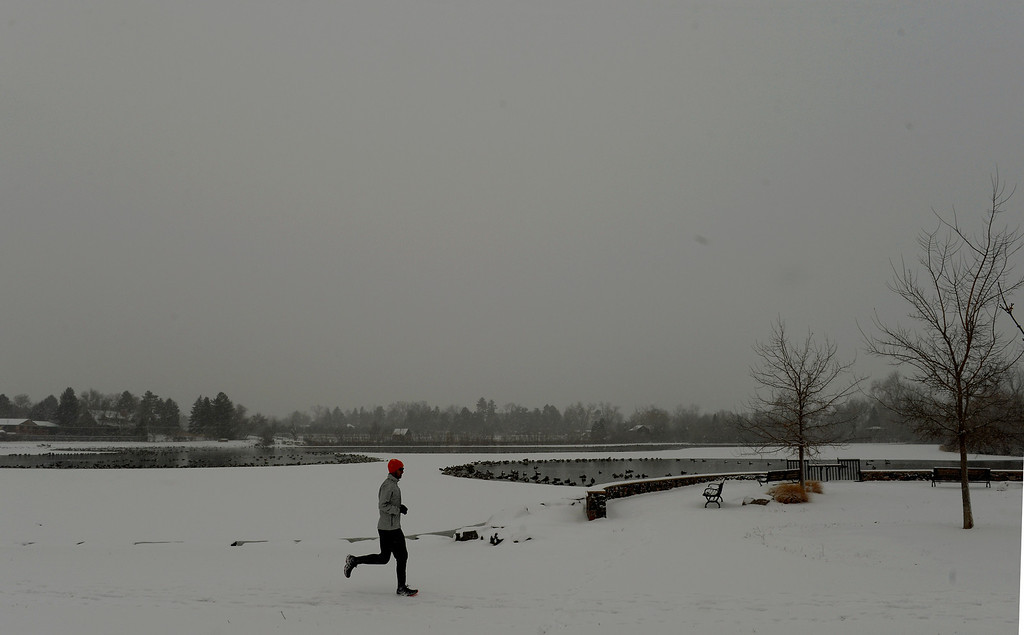 . LITTLETON, CO. - JANUARY 04: A jogger passes through Ketring Park in Littleton, CO January 04, 2014. Temperatures will linger in the low 20s Saturday as a storm drops anywhere from 3 to 5 inches of snow in the Denver metro area, forecasters say.(Photo By Craig F. Walker / The Denver Post)