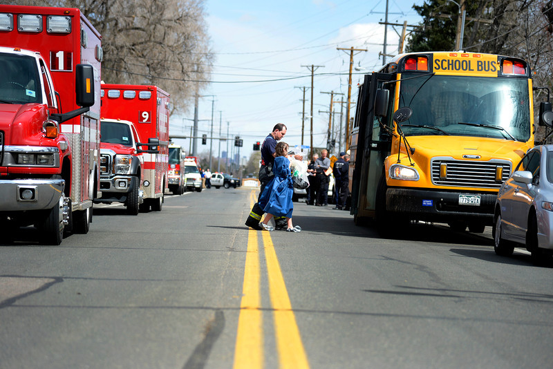. LAKEWOOD, CO - APRIL 07: A West Metro firefighter leads a student to a bus full of evacuees during an evacuation after students were exposed to hazardous skin irritants. Jeffco Open School evacuation on Monday, April 8, 2014. (Photo by AAron Ontiveroz/The Denver Post)