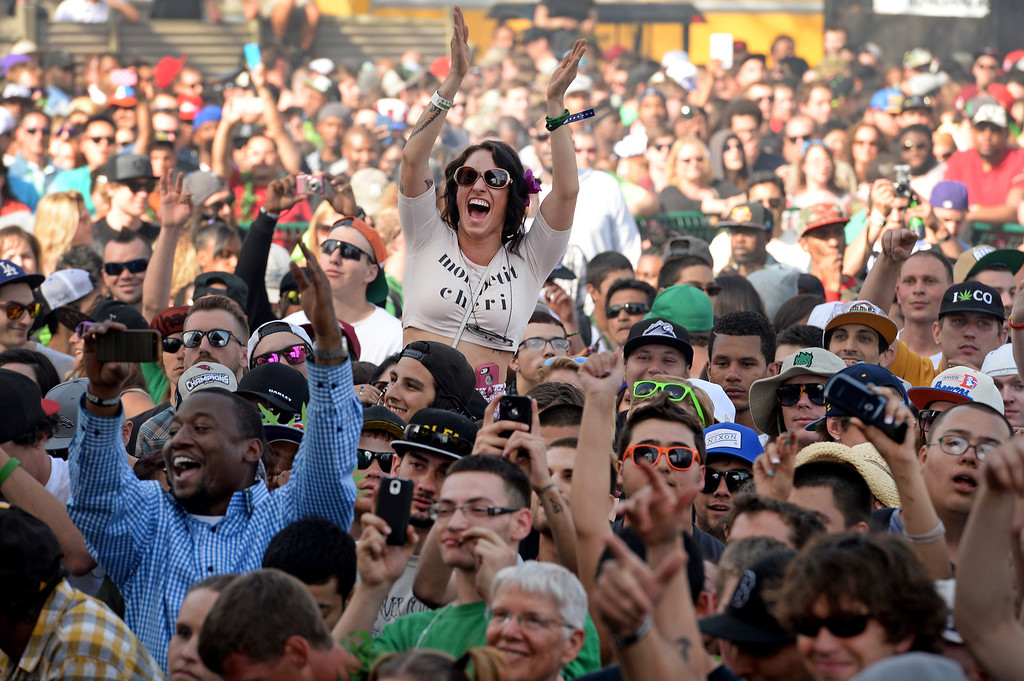 . People in the audience cheer for rap singer B.o.B.as he performs for thousands during the Colorado 420 Rally at Civic Center Park in Denver on April 20, 2014.  Thousands of people lit up marijuana pipes, cigarettes, joints, and bongs at exactly 4:20 pm to celebrate the now legal use of marijuana in the state of Colorado.  (Photo By Helen H. Richardson/ The Denver Post)