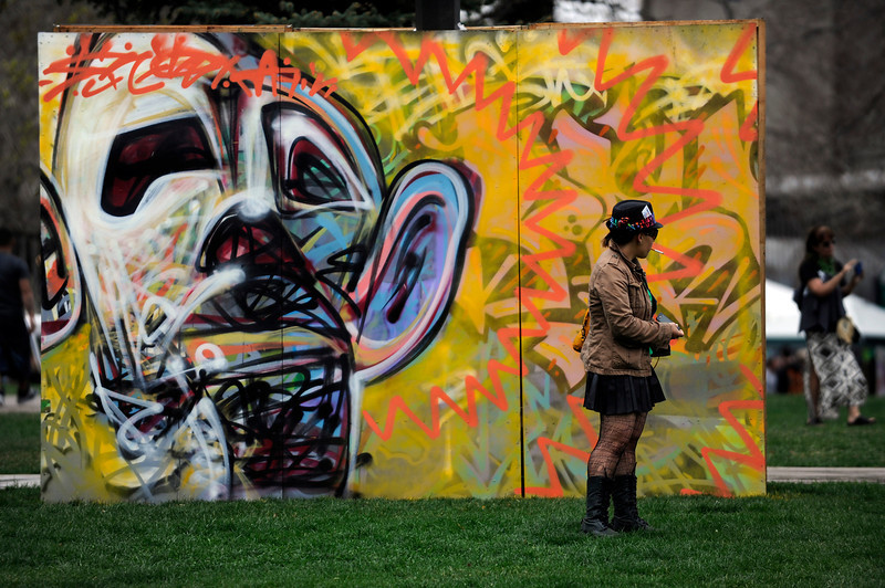 . A woman takes a cigarette break in front of a mural during the 420 Rally at Civic Center Park in Denver, Colorado on April 19, 2014. (Photo by Seth McConnell/The Denver Post)