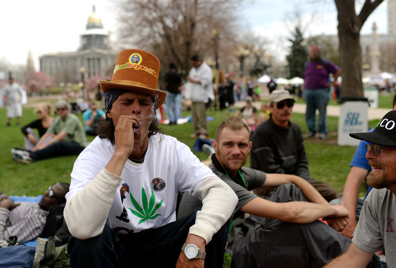 . J.D. from South Dakota is smoking marijuana during the first day of the 420 Rally weekend in Civic Center Park, Denver, Colorado, April 19, 2014. (Photo by Hyoung Chang/The Denver Post)