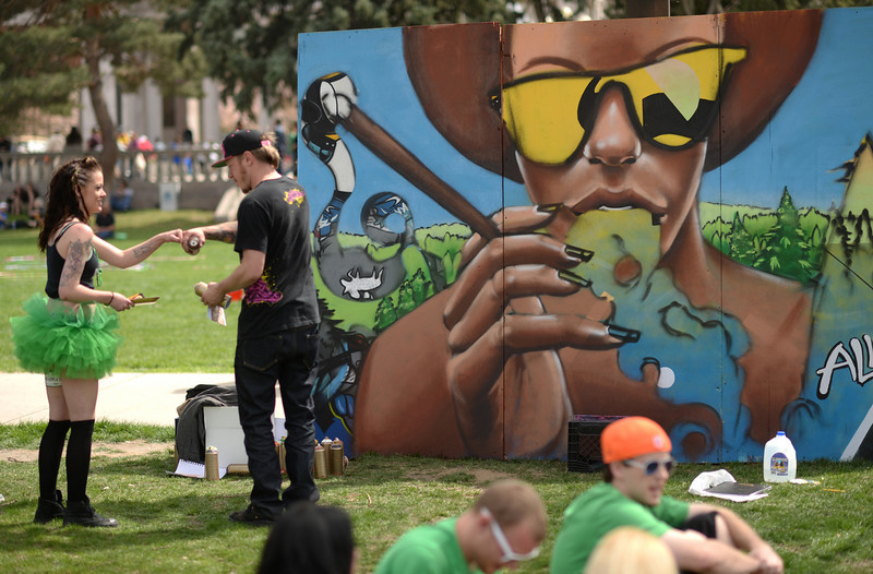 . Artist Robin Muruno, top right, celebrates finishing his splay painting work with Chenoa Klakowicz, left, during the first day of the 420 Rally weekend in Civic Center Park, Denver, Colorado, April 19, 2014. (Photo by Hyoung Chang/The Denver Post)