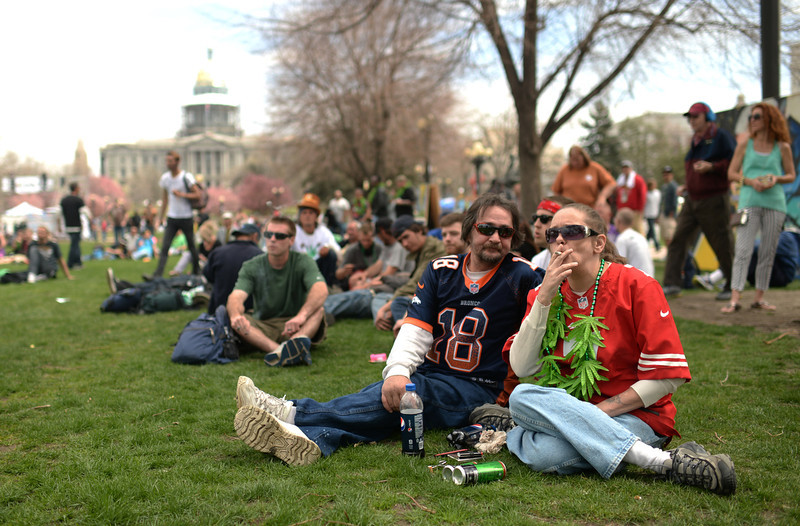 . Margaret Henry of Denver, right, smokes marijuana with her boyfriend Wililam Lagrand during the first day of the 420 Rally weekend in Civic Center Park, Denver, Colorado, April 19, 2014. (Photo by Hyoung Chang/The Denver Post)