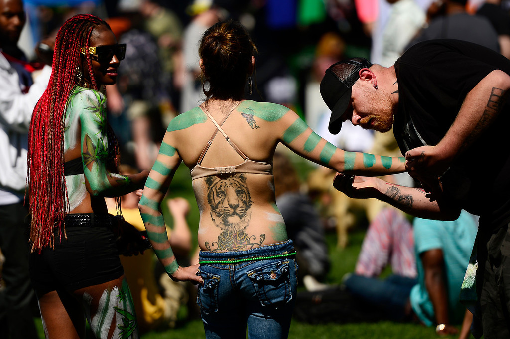 . Chanti Sisson 28 of Aurora is painted by Ryan Winckler 30 of Denver as LaTosha Taylor 30 of Denver looks on during the 420 celebration at the Denver 420 Rally in Civic Center Park April 20, 2014 Denver, CO (Photo By Joe Amon/The Denver Post)