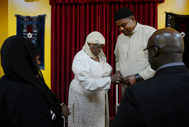 . Billy Wheelock, right, puts a wedding ring on his wife\'s finger, Berna Wheelock while Berna\'s daughter, Tonya Lang, left, and Tonya\'s fiancee, Charles Blakney, right, witness the occasion at the Northeast Denver Islamic Center Saturday, April 19, 2014. On Thursday April 17, 2014, Billy Wheelock became a free man after serving 21-years of a life sentence on drug charges, thanks to President Obama, who granted Wheelock clemency December 19, 2013. (Photo By Andy Cross / The Denver Post)