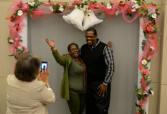 . Billy Wheelock, right, and his fiancee, Berna Lang, get their picture taken by Tina Romero, community partnership specialist at the Denver Office of the Clerk and Recorder Thursday afternoon, April 17, 2014, after picking up their marriage license. Earlier in the morning, Wheelock walked out of a Denver halfway house a free man after getting his ankle monitor cut off. Wheelock was granted clemency by the President of the United States after serving 21-years of a life sentence for drug charges occurred in Texas. Wheelock and Lang were married on Saturday, April 19. (Photo By Andy Cross / The Denver Post)